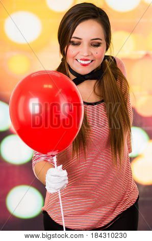 Closeup portrait of cute hispanic young girl clown mime holding red balloon