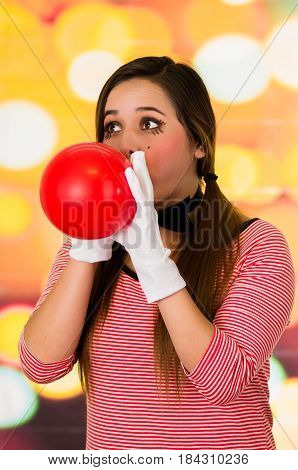 Closeup portrait of cute young girl clown mime blowing a balloon