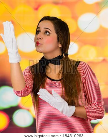 Closeup portrait of cute beautiful young girl clown mime sending kiss