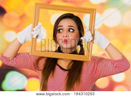 Closeup portrait of cute curious young girl clown mime holding wooden frame looking to the side, looking confused
