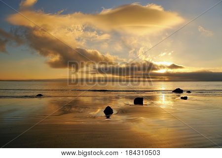 Sunrise and golden clouds with reflection. Tasman Sea, New Zealand