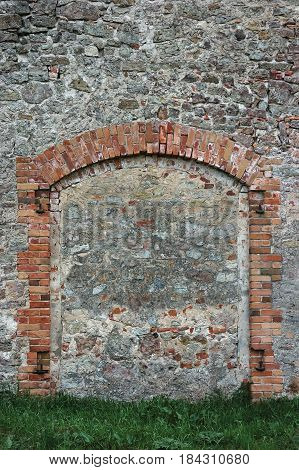 Barn gate door fake false faux arch, stone wall background frame closeup, vertical limestone copy space, green grass, plastered grunge red brick stonewall pattern, old aged weathered beige lime plaster texture, natural grungy textured reddish vintage roug