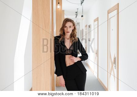 Pretty woman in suit and bra posing in apartm?nt while holding arm at hip and looking at the camera