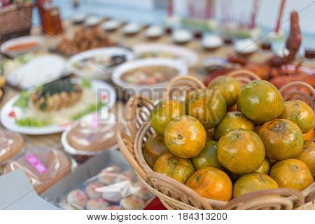 Close focus on sweet orange in basket with blurry food set for making a ancestor spirit offering in Chinese style.