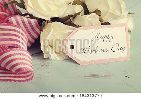 Happy Mothers Day white roses gift on vintage background  Retro style Happy Mothers Day gift of white roses bouquet with pink stripe ribbon and gift tag with greeting on aqua blue vintage shabby chic table.