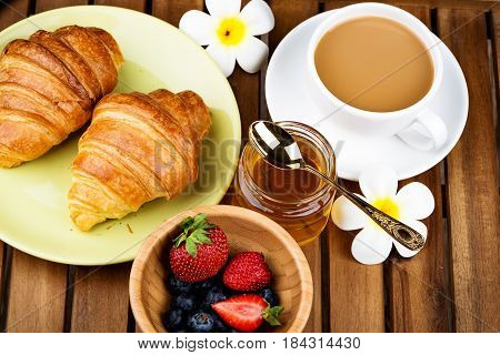 Cup of coffee and croissants on wooden background.
