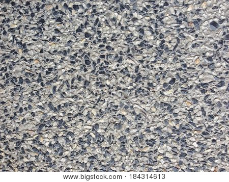 Cement mixed small gravel stone wall or floor abstract texture background.Random pebble gravel oval elements seamless pattern.
