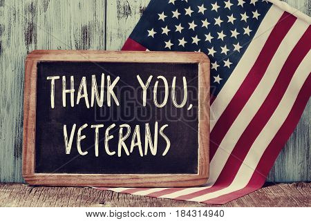 the text thank you veterans written in a chalkboard and a flag of the United States on a rustic wooden background