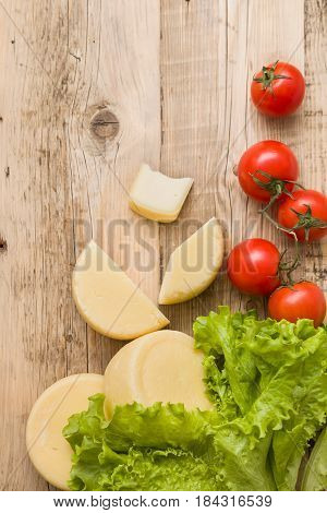 Top view on cut cheese heads on wooden board served with tomatoes and fresh salad. Serving French homemade cheese. Food concept
