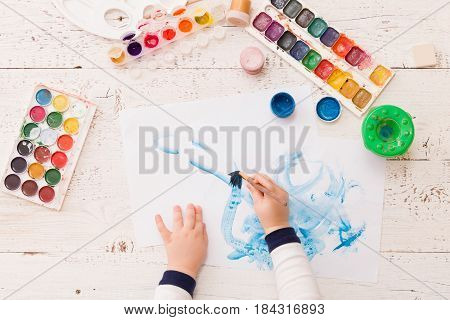 Top view on child's hands drawing. Colorful picture made by a toddler boy. Creative ideas and learning. Education concept.