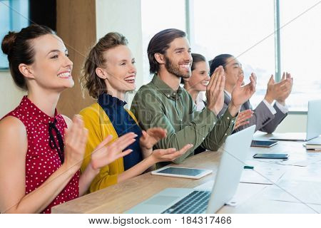 Business team applauding during meeting in conference room at office