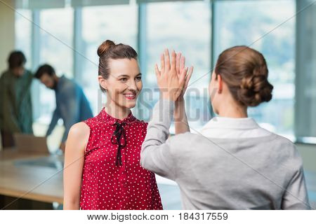 Business executives giving high five to each other in office