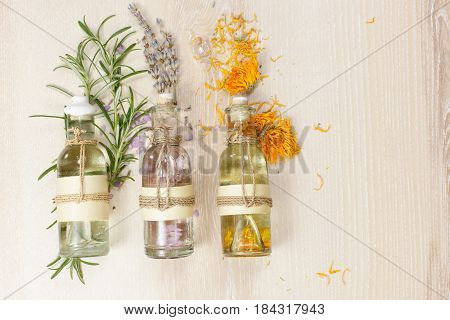 Aromatherapy massage oils and plants on wooden background