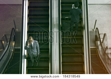 Business people using escalator and talking phone