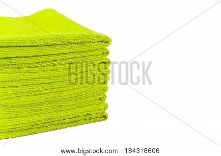 the green terry towels laid by a pile on a white background