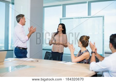 colleagues clapping for businesswoman in conference room at office