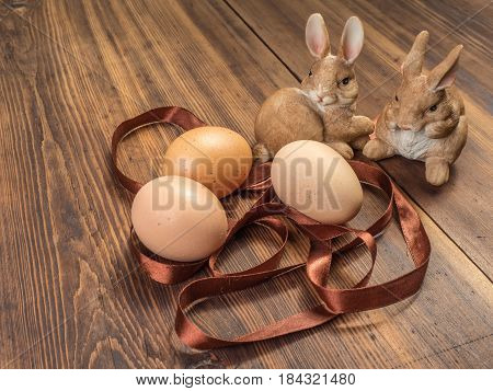 Easter bunnies on the background of wooden table from the old boards with ribbon and brown chicken eggs. Background in rustic style for advertising or Easter greetings