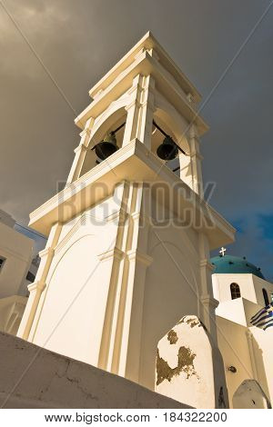 Bell tower and a blue dome of a church at sunset, Imerovigli village, Santorini island, Greece