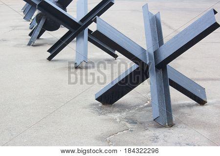 Steel anti-tank obstacles barrier black on the asphalt
