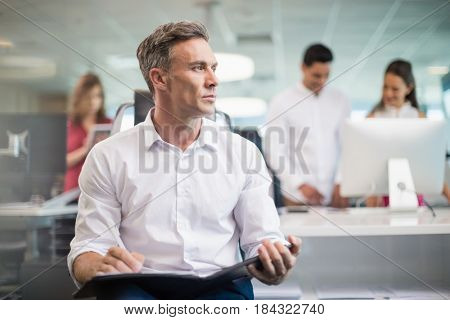 Thoughtful business executive sitting on chair and writing on clipboard in office