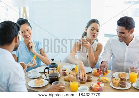 Business colleagues interacting with each other while having breakfast in office cafeteria