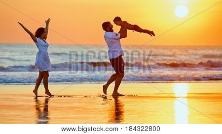Happy family - father mother baby son walk with fun along edge of sunset sea surf on black sand beach. Active parents and people outdoor activity on summer vacations with children on Bali island