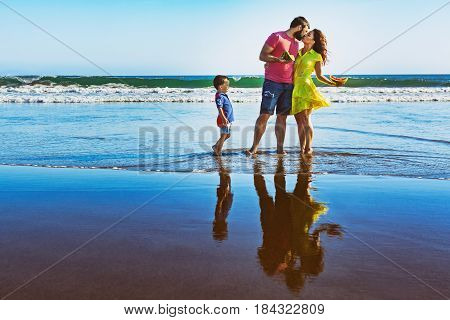 Happy family - father, mother, baby son walk by water pool on black sand beach with sea surf. People have picnic - eat tropical fruits. Travel, active lifestyle, parents with child on summer vacation.