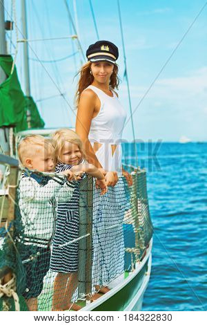 Happy family - mother in captain cap baby son daughter on board of sailing yacht. Children have fun discovering islands in summer cruise. Travel adventure yachting with kids on family vacation.