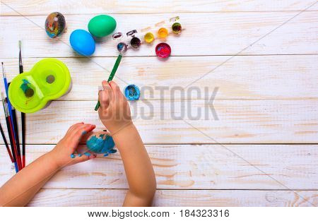 Happy easter. Kid  painting Easter eggs. Top view on white wooden table