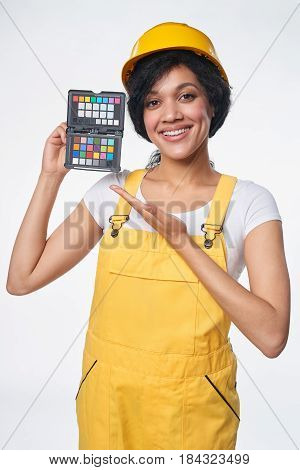 Smiling mixed race woman builder wearing yellow protect helmet and overall showing color checker, over white background