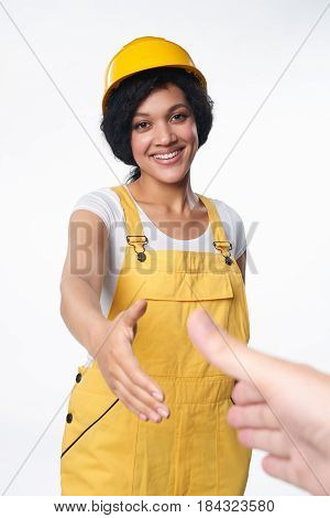 Smiling mixed race construction woman wearing yellow protect helmet and overall shaking hands sealing a deal, over white background