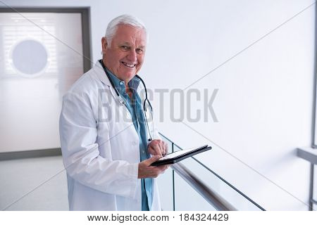 Portrait of doctor using a digital tablet in the passageway at hospital