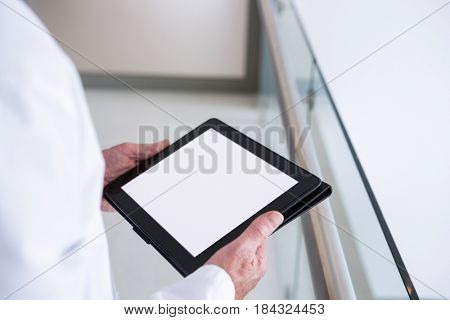 Close-up of doctor using a digital tablet in the passageway at hospital