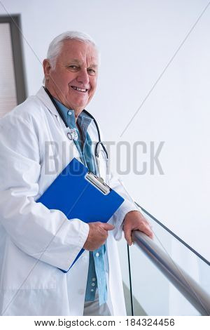 Portrait of doctor holding clipboard in the passageway