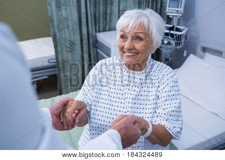 Senior patient taking assistance from the doctor at hospital