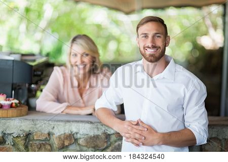 Portrait of waiter and customer standing at counter at restaurant