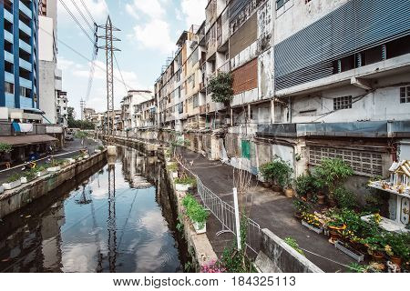 Bangkok old city view, Thailand. Small rural road with traditional houses, green lush trees near small lazy river and parked motorbike at sunny day, outdoor city landscape