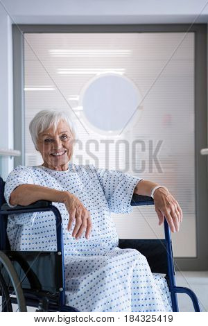 Portrait of disabled senior patient on wheelchair in hospital corridor at hospital