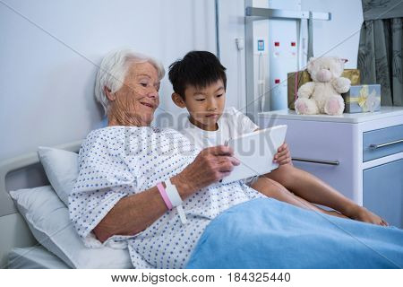 Senior patient and boy holding digital tablet at hospital