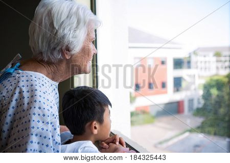 Senior patient and boy looking out from the window at hospital