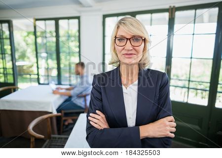 Portrait of businesswoman standing with arms crossed in a restaurant
