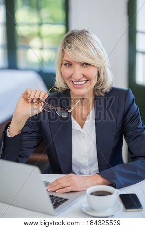 Portrait of businesswoman using laptop in a restaurant