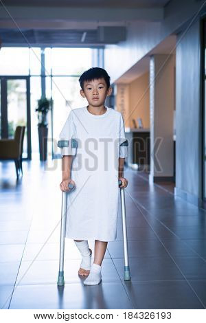 Boy patient walking with crutches in corridor at hospital