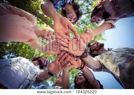 Smiling friends forming a handstack in park on a sunny day