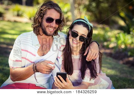 Woman showing mobile phone to man in park on a sunny day