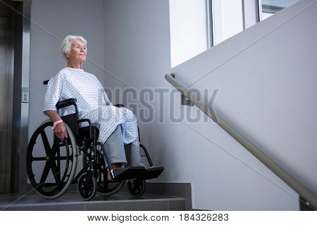 Disabled senior patient on wheelchair near staircase in hospital