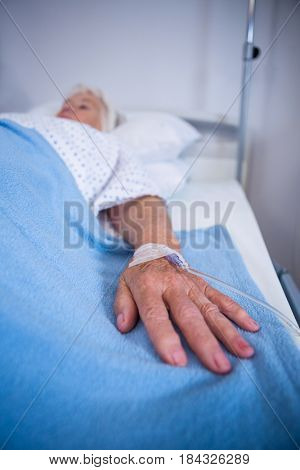 Close-up of senior patient hand with saline on bed in hospital
