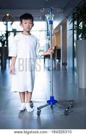 Boy patient holding intravenous iv drip stand in corridor at hospital
