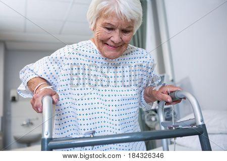 Smiling senior patient holding walking frame at hospital