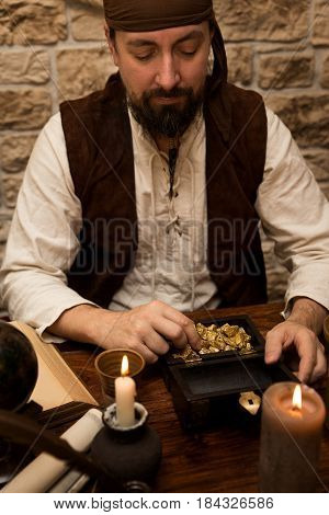 a Pirate with big prey table with treasure of gold candles and vintage decoration
